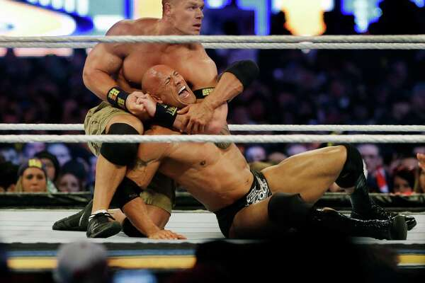 FILE -In a Sunday, April 7, 2013 file photo, wrestler John Cena, top, chokes Dwayne Douglas Johnson, known as The Rock as they wrestle during Wrestlemania, in East Rutherford, N.J. WWE bills WrestleMania as its Super Bowl, and is headed to a stadium worthy of a Super Bowl on Sunday, April 3, 2016.  The WWE has lofty expectations of stuffing 100,000 fans inside AT&T Stadium in Arlington, Texas.  (AP Photo/Mel Evans, File)