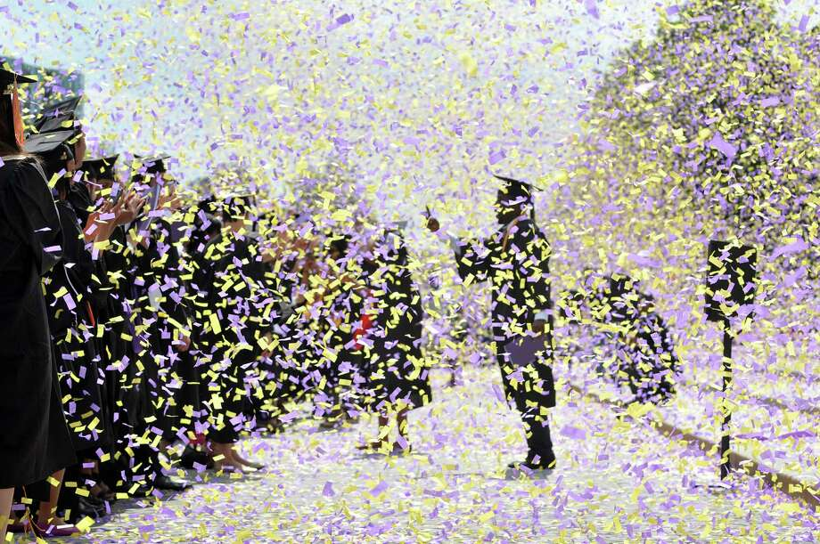 Confetti spills over the graduates as they receive degrees during the University at Albany commencement on Sunday, May 17, 2015, in Albany, N.Y.    (Paul Buckowski / Times Union) Photo: PAUL BUCKOWSKI / 00031518A