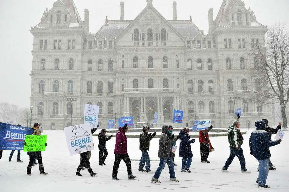 Supporters of Bernie Sanders march through the snow during a rally outside the Capitol on Monday, April 4, 2016, in Albany, N.Y.  (Paul Buckowski / Times Union) Photo: PAUL BUCKOWSKI / 10036053A