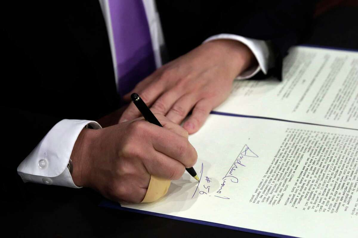 New York Gov. Andrew Cuomo, signs a law that will gradually raise New York's minimum wage to $15, at the Javits Convention Center, in New York, Monday, April 4, 2016. (AP Photo/Richard Drew, Pool) ORG XMIT: NYRD304