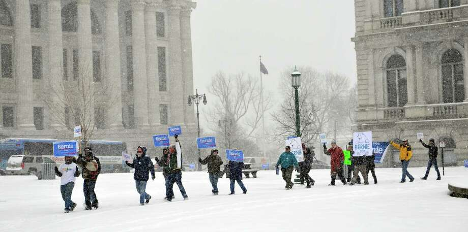 Supporters of Bernie Sanders march through the snow during a rally outside the Capitol on Monday, April 4, 2016, in Albany, N.Y.  (Paul Buckowski / Times Union) Photo: PAUL BUCKOWSKI / 10036056A