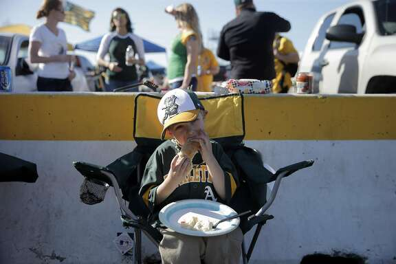 Zachary Haynes, 5, eats a hot dot in the parking lot before the A's played the Chicago White Sox as fans gathered outside the Oakland Coliseum in Oakland, Calif., on Monday, April 4, 2016.