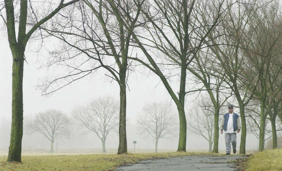 FILE - In this March 5, 2004 file photo, a man walks along a path lined with elm trees in Princeton, N.J.. The recent spring-like weather has a big downside for allergy sufferers: Tree buds, the first being elms and maples, have begun releasing pollen ahead of the normal time. A report issued Monday, April 4, 2016, by the Obama Administration listed how global warming will make the air dirtier, water more contaminated and food more tainted. It warned of diseases, such as those spread by ticks and mosquitoes, longer allergy seasons, and thousands of heat wave deaths.  (AP Photo/Daniel Hulshizer, File) Photo: Daniel Hulshizer, STF / AP