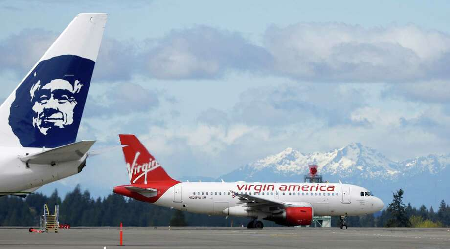 A Virgin America Airbus taxis past one of Alaska Airlines' Boeing jets at Seattle-Tacoma International Airport. Photo: Ted S. Warren, STF