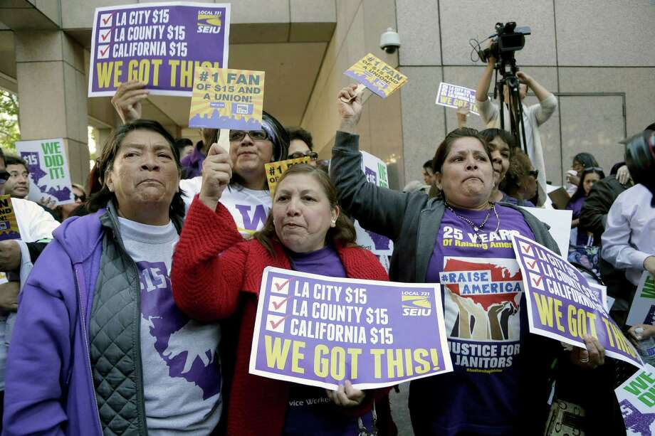 Workers rally outside the Ronald Reagan State Building in Los Angeles after California's Gov. Jerry Brown signed a bill creating highest statewide minimum wage at $15 an hour by 2022 in Los Angeles, Monday, April 4, 2016. California and New York acted Monday to gradually push their statewide minimum wages to $15 an hour, the highest level in the nation. (AP Photo/Nick Ut) Photo: Nick Ut, STF