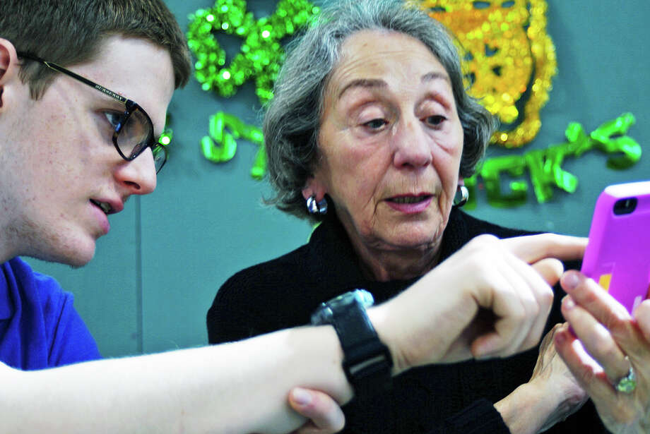 Sean Oppeheimer helps Fortuna Mangieri figure out how her iPhone works during a free tutoring session at the Bigelow Center for Senior Activities. Photo: Genevieve Reilly / Hearst Connecticut Media / Fairfield Citizen