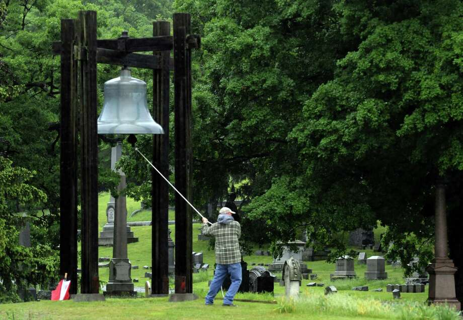 Jerry Kehn rings the Vanderheyden Memorial Bell to start The Veterans of Lansingburgh, Inc. Memorial Day weekend ceremony at Oakwood Cemetery on Saturday May 25, 2013 in Troy, N.Y. (Michael P. Farrell/Times Union) Photo: Michael P. Farrell / 00022525B