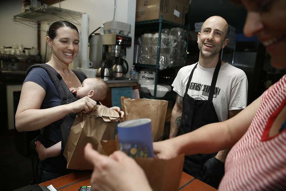 Co-owners Christina Stobing (left), with her 6-month-old daughter, and Peter Fikaris work at their vegan deli the Butcher's Son in Berkeley. Photo: Liz Hafalia, The Chronicle