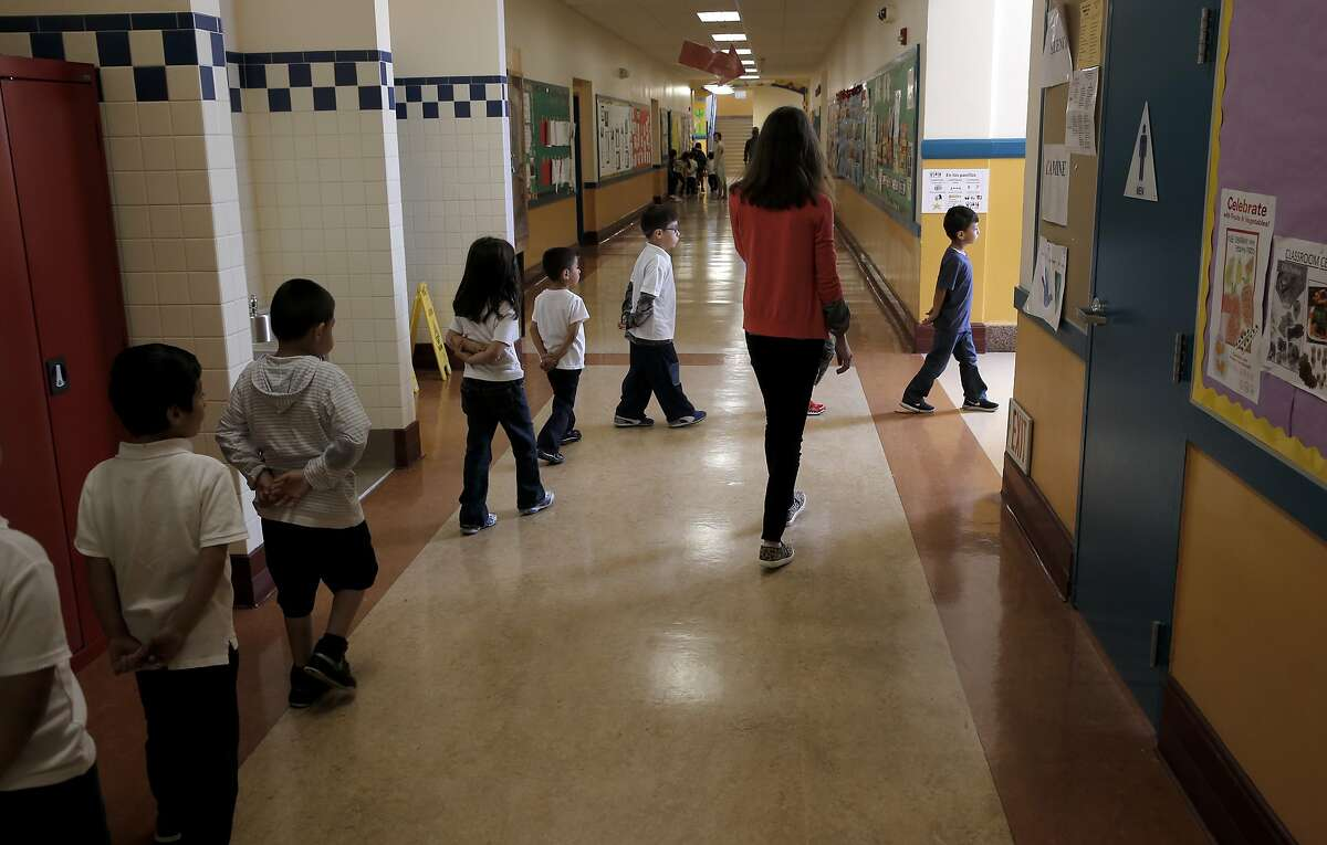 Kindergarten teacher Rebecca Sheehan-Stross, guides her students out to recess at Cesar Chavez Elementary school in San Francisco, California, on Tues. April 5, 2016. Kindergarten teacher Sheehan-Stross is considering leaving the district after one more school year because she can only afford to rent a dining room in Oakland with no closets and doors that don't close.