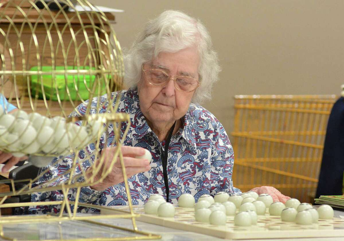 Grace Blades, of The Woodlands, adds numbered balls to the master board she uses to verify winning bingo boards during Bingo for senior citizens at the South County Community Center, 2235 Lake Robbins Drive. Interfaith of The Woodlands sponsors the bingo day. Photograph by David Hopper