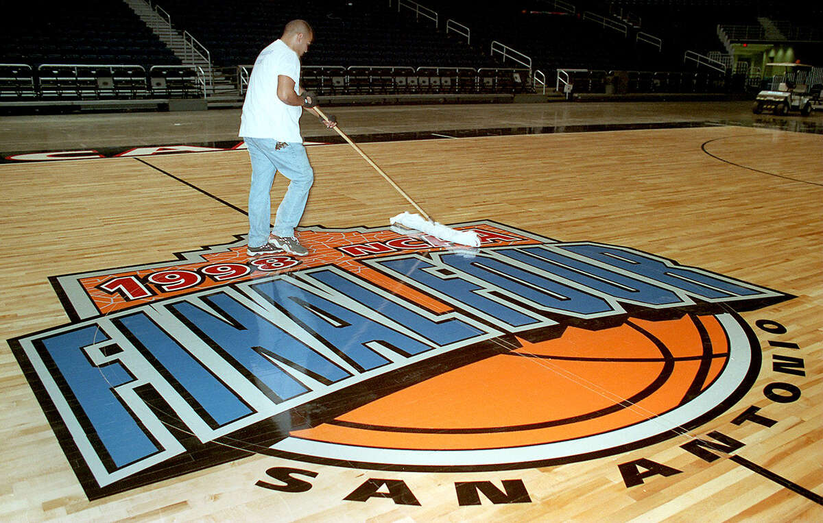 Robert Sanchez sweeps the basketball court at the Alamodome. The floor for the NCAA Men's Final Four was put down on March 23, 1998.