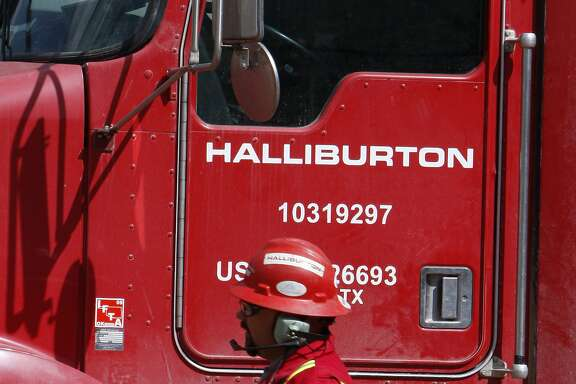 In this April 15, 2009, file photo, an unidentified worker passes a truck owned by Halliburton at a remote site for natural-gas producer Williams in Rulison, Colo. Halliburton is buying rival oilfield services company Baker Hughes in a cash-and-stock deal worth $34.6 billion. The deal comes shortly after talks had stalled and Halliburton prepared to go hostile with its takeover bid. (AP Photo/David Zalubowski, File)