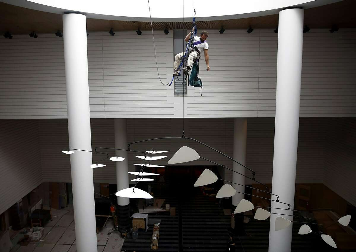Lawrence LaBianca climbs back up to the top of the museum after repelling down to finish the installation of an Alexander Calder mobile at the Museum of Modern Art in San Francisco, California, on Tuesday, April 5, 2016.