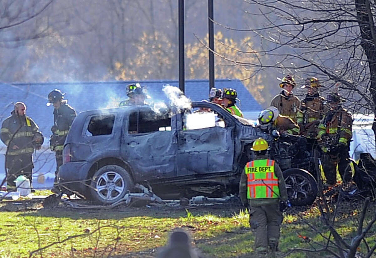 Emergency responders at the scene of a vehicle fire in a wooded area north of the Darien rest stop on I-95 south Tuesday.
