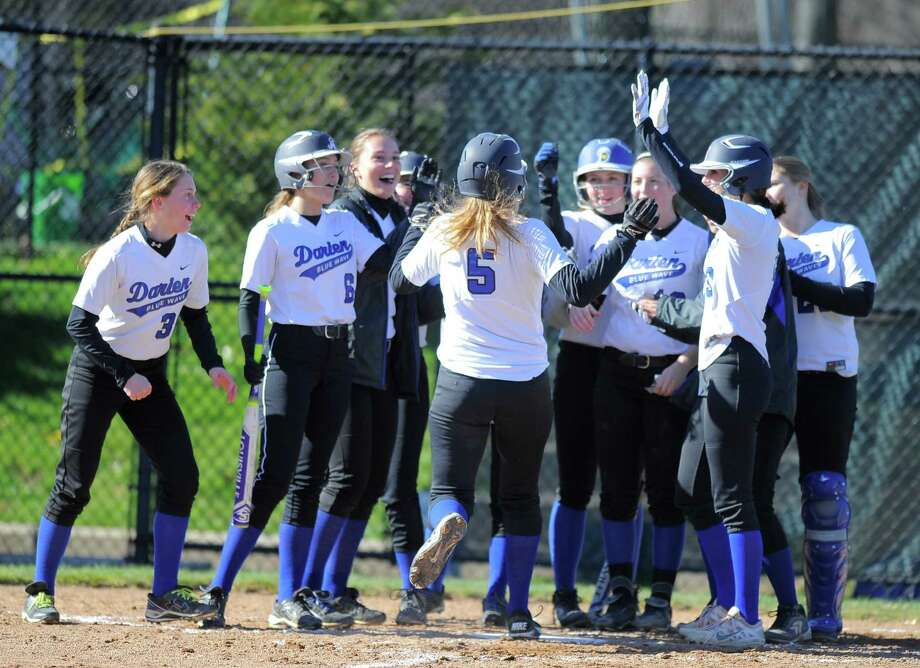 Darien's Cassie Lopiano is greeted at homeplate by her teammates following a second-inning three-run home run in a 14-2 win over Danbury on Tuesday. Photo: Matthew Brown / Hearst Connecticut Media / Stamford Advocate
