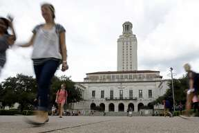 FILE - In this Sept. 27, 2012 file photo, students walk through the University of Texas at Austin campus near the school's iconic tower in Austin, Texas. The cost of funding higher education for veterans has increased sevenfold since Texas legislators allowed veterans to pass the benefit onto a child. (AP Photo/Eric Gay, File)