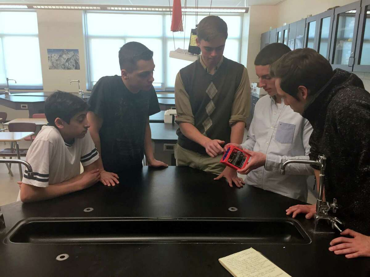 Gloversville High School student scientists, from left, Rami Haddawi, Tyler Benton, Austin Reese, Matthew Helou and Nicholas Brock. Helou is holding the CubeSat model as Reese explains the different parts. (Danielle Ferrari/Special to the Times Union)