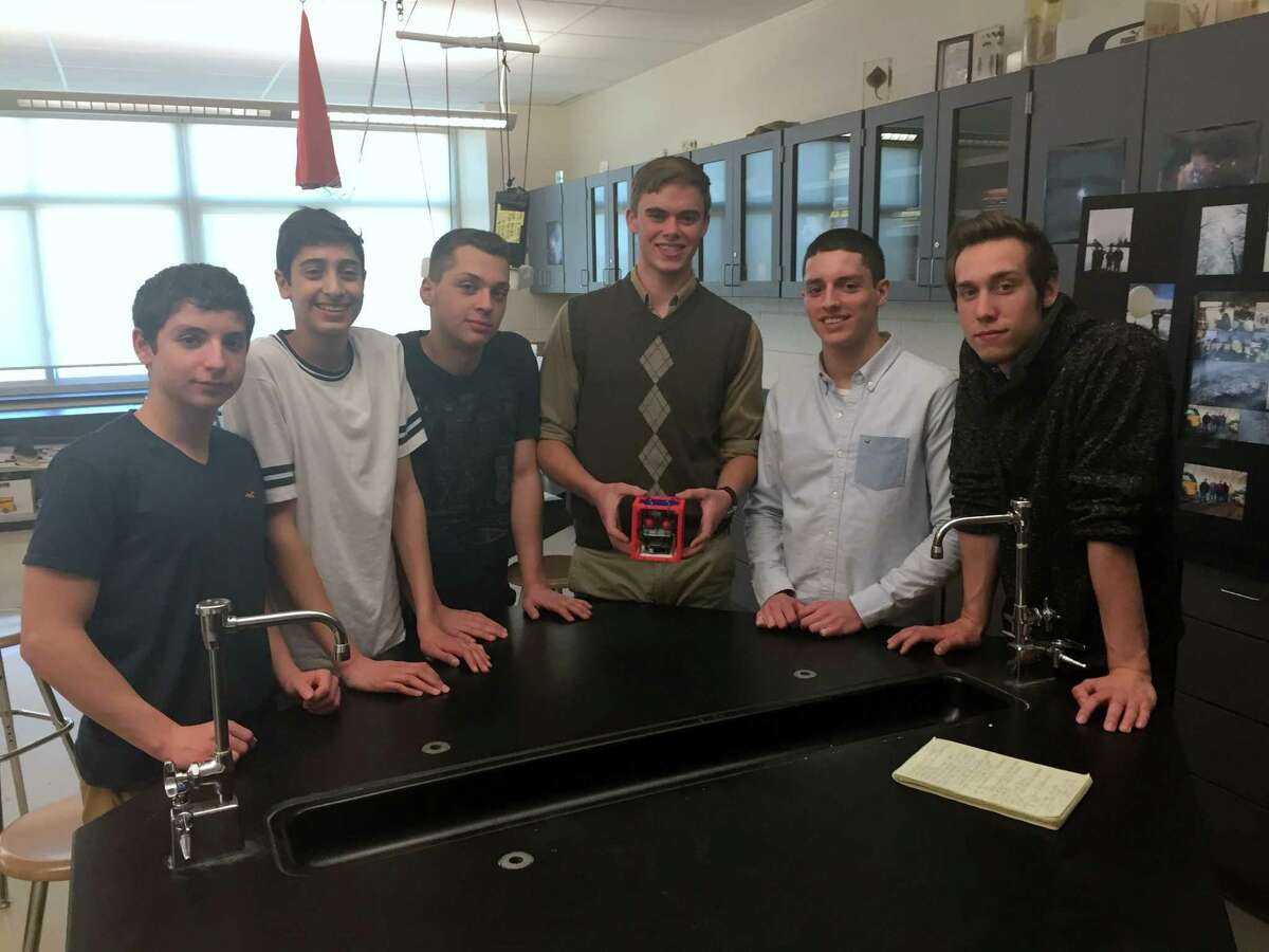 Gloversville High School student scientists, from left, Danny Helou, Rami Haddawi, Tyler Benton, Austin Reese, Matthew Helou and Nicholas Brock. Reese is holding the CubeSat experiment model that will be flying on the Airborne Perlan Mission II. (Danielle Ferrari/Special to the Times Union)