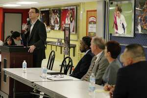 State education commissioner Mike Morath (left) addresses a crowded room of parents and educators from Edgewood Independent School District in 2016. The appointed Edgewood board should have let Morath fill a vacated seat.