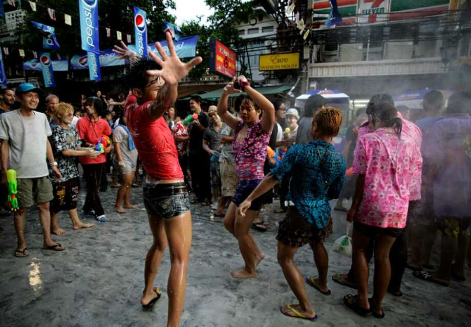 BANGKOK, THAILAND - APRIL 13: Tourists and Thai people celebrate on the first of three days of Songkran New Year festival, amid the political turmoil of weeks of protests and more recently, clashes with the Thai military, at Khao Sarn Road  on April 13, 2010 in Bangkok, Thailand. Thailand's foreign minister Kasit Piromya ruled out any immediate role for ousted former Prime Minister Thaksin Shinawatra at a global nuclear summit in Washington last night, with US Secretary of State Hillary Clinton urging Thailand to instead embrace reconciliation.  (Photo by Luis Ascui/Getty Images) Photo: Luis Ascui, Getty Images / 2010 Getty Images