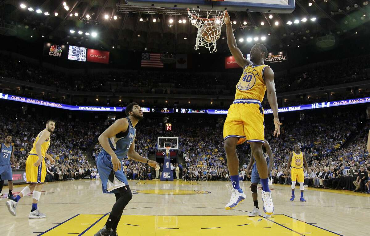 Golden State Warriors' Harrison Barnes (40) dunks in front of Minnesota Timberwolves' Karl-Anthony Towns during the first half of an NBA basketball game Tuesday, April 5, 2016, in Oakland, Calif.