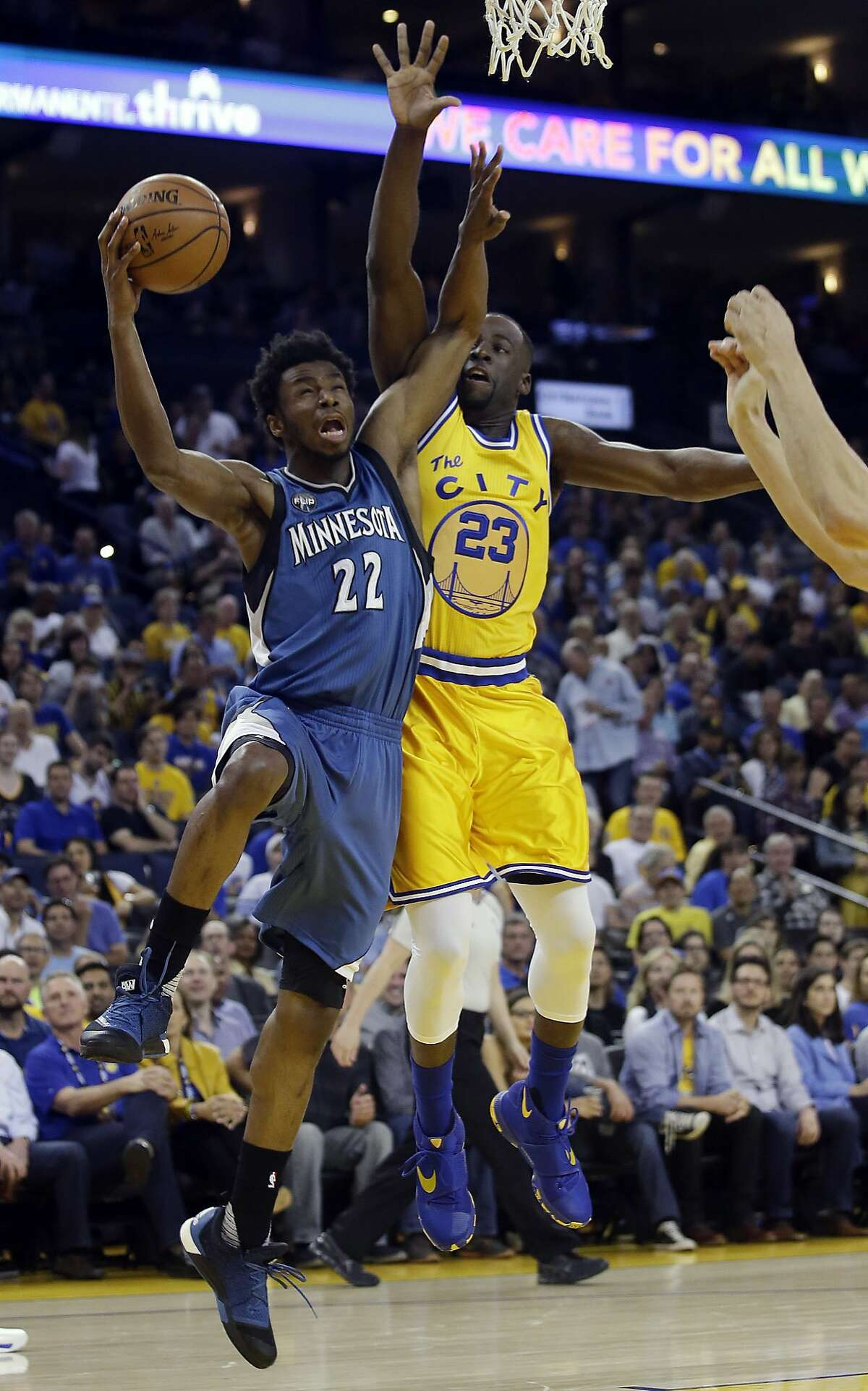 Minnesota Timberwolves' Andrew Wiggins (22) drives to the basket as Golden State Warriors' Draymond Green (23) defends during the first half of an NBA basketball game Tuesday, April 5, 2016, in Oakland, Calif.