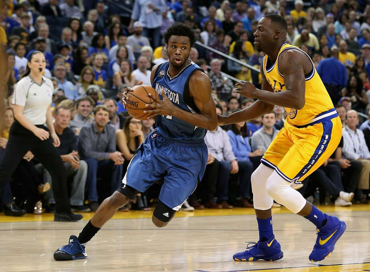Andrew Wiggins #22 of the Minnesota Timberwolves drives on Draymond Green #23 of the Golden State Warriors at ORACLE Arena on April 5, 2016 in Oakland, California. NOTE TO USER: User expressly acknowledges and agrees that, by downloading and or using this photograph, User is consenting to the terms and conditions of the Getty Images License Agreement. (Photo by Ezra Shaw/Getty Images)