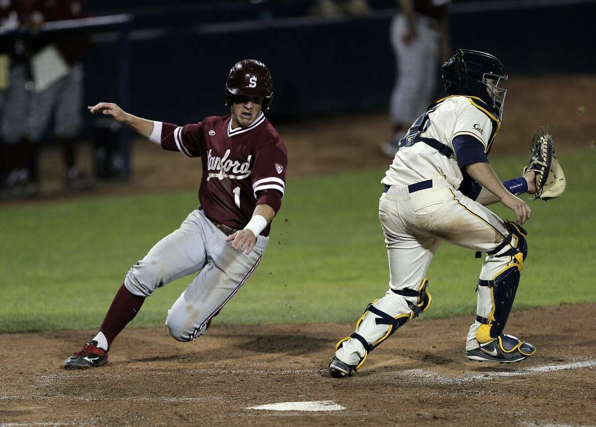 Mikey Diekroeger (1) slips around Cal catcher Brett Cumberland (28) to score in the sixth inning as the California Golden Bears played the Stanford Cardinal at Evans Diamond in Berkeley, Calif., on Tuesday, April 5, 2016.