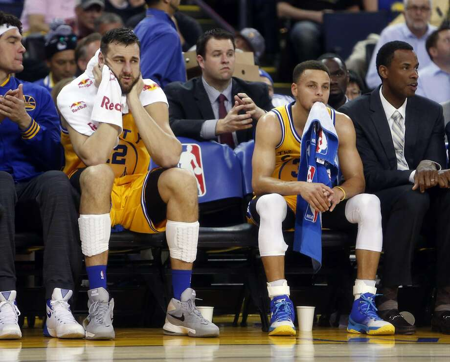 Andrew Bogut (12) and Stephen Curry watch from the bench as the Warriors play Minnesota. Golden State blew a 17-point lead against one of the NBA's worst teams and lost in overtime. Photo: Scott Strazzante, The Chronicle