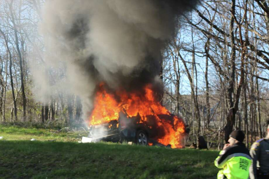 A car driven by a Bridgeport man burns after crashing into trees near the Darien rest area on I-95 on Tuesday, April 5, 2016. Jimmy Munoz, 35, of Bridgeport was pronounced dead at the scene. Photo: Thor Deegan /Contributed Photo