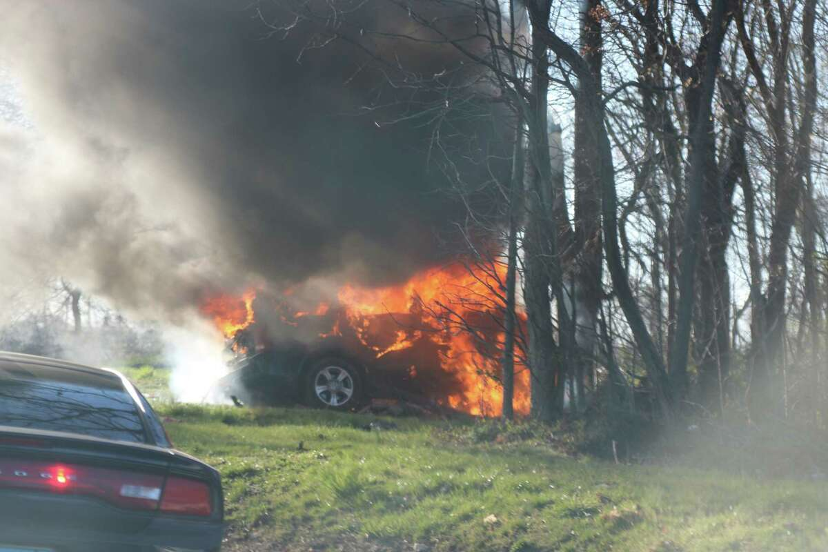 A car driven by a Bridgeport man burns after crashing into trees near the Darien rest area on I-95 on Tuesday, April 5, 2016. Jimmy Munoz, 35, of Bridgeport was pronounced dead at the scene.