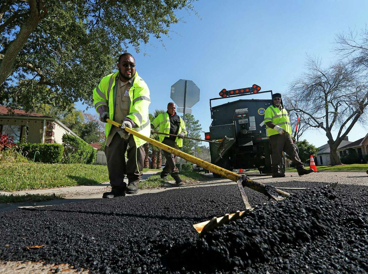 Robert Poole uses a rake to smooth hot asphalt as he and fellow City of Houston crew members Timothy Drones and Charles Clophus fill a pothole.