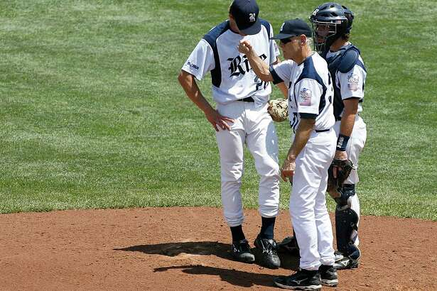 OMAHA, NE - JUNE 20:  Catcher Danny Lehmann #11 (R) and starting pitcher Ryan Berry #28 of the Rice Owls (L) stand as head coach Wayne Graham (C) calls for a relief pitcher against North Carolina during the Tar Heels 6-1 win in Game 11 of the NCAA College World Series at Rosenblatt Stadium on June 20, 2007 in Omaha, Nebraska.