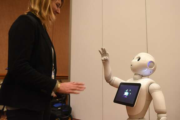 Pepper, a humanoid robot by Aldebaran Robotics and SoftBank Mobile, interacts with Aurore Chiquot, in the media room during CES Press Day, January 5, 2016 in Las Vegas, Nevada ahead of the CES 2016 Consumer Electronics Show. Pepper is a social robot created to converse, recognize and react to emotions.  AFP PHOTO / ROBYN BECK / AFP / ROBYN BECK        (Photo credit should read ROBYN BECK/AFP/Getty Images)