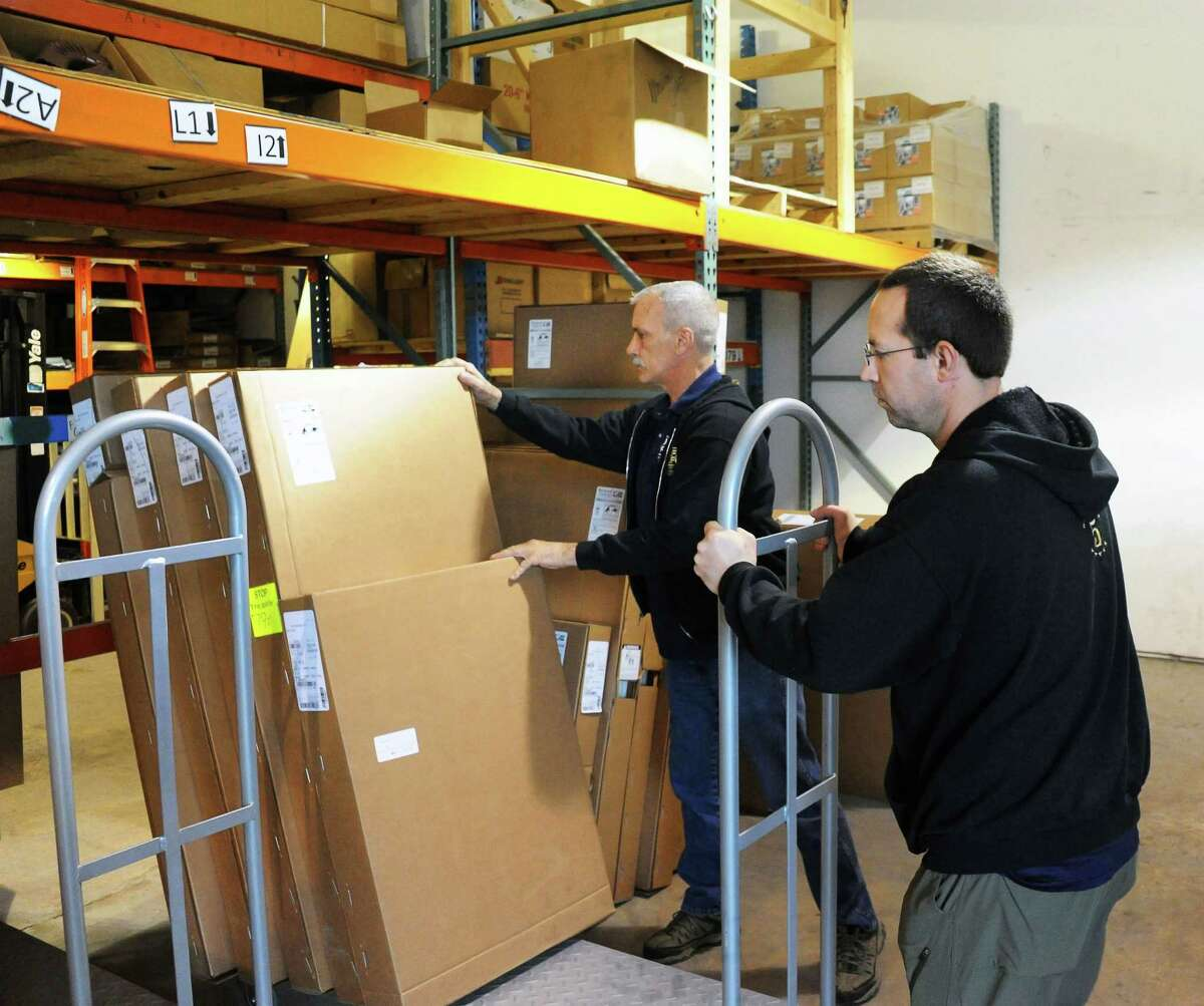 Huff 'N Puff gutter installation manager Ed McElroy, left, and warehouse manager Jim Lawyer in the warehouse at their Rotterdam Industrial Park facility Thursday March 10, 2016 in Rotterdam, NY. (John Carl D'Annibale / Times Union)