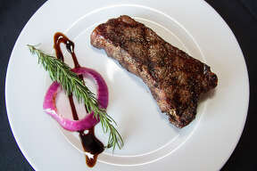 The grilled New York Strip steak is served with a red onion ring, sliver of rosemary and drizzle of balsamic glaze.