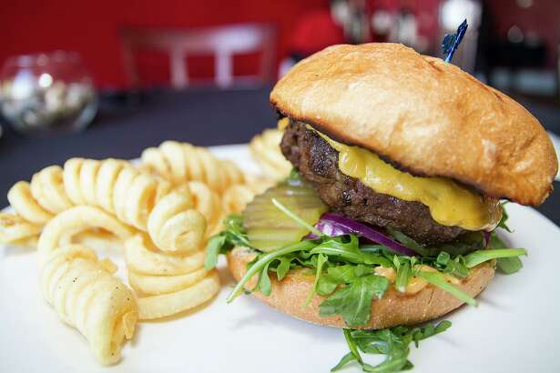 The Kobe burger includes American cheese, arugula, tomatoes, red onion and chipotle mayonnaise, and is served with curly fries.