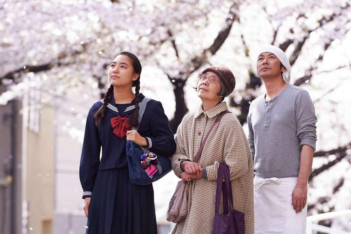 "Wakana (Kyara Uchida, left), a girl from a troubled home; Tokue (Kirin Kiki), whose red bean paste satisfies; and Sentaro (Masatoshi Nagase), whose dorayaki shop turns the corner when Tokue's secret recipe brings in customers, in the film ""Sweet Bean."""