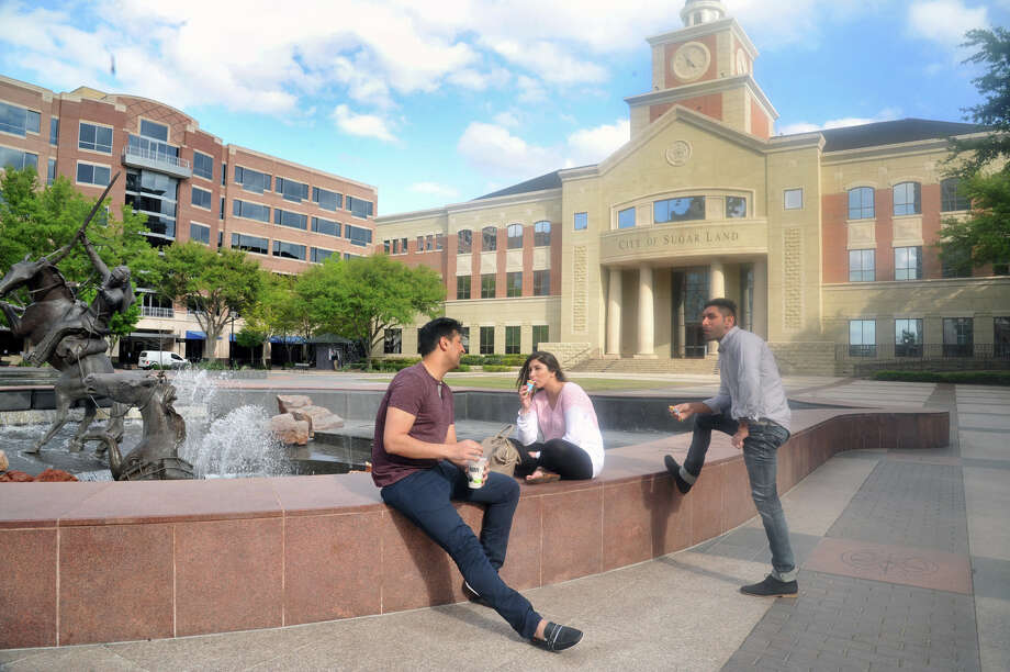 Visitors to businesses and City Hall at Sugar Land Town Square reflect Fort Bend County's ethnic diversity. Jay Shaitid, left, chats with Jessica and Vicey Michaels at the fountain in front of City Hall.  Photo: Eddy Matchette, Freelance / Freelance