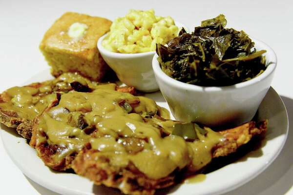 Smothered pork chops with sides of cornbread, macaroni and cheese and greens at Carmi Soul Food in Pittsburgh. (Pam Panchak/Pittsburgh Post-Gazette/TNS) ORG XMIT: 1182452