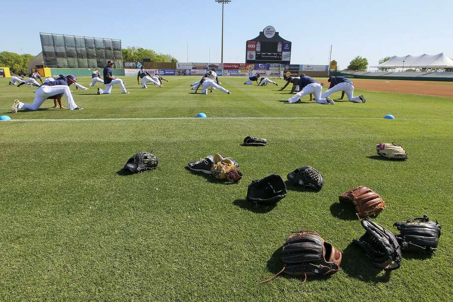Players leave their gloves on the field as they stretch during the first day of practice for the San Antonio Missions at Wolff Stadium onApril 5, 2016. Photo: Marvin Pfeiffer /San Antonio Express-News / Express-News 2016