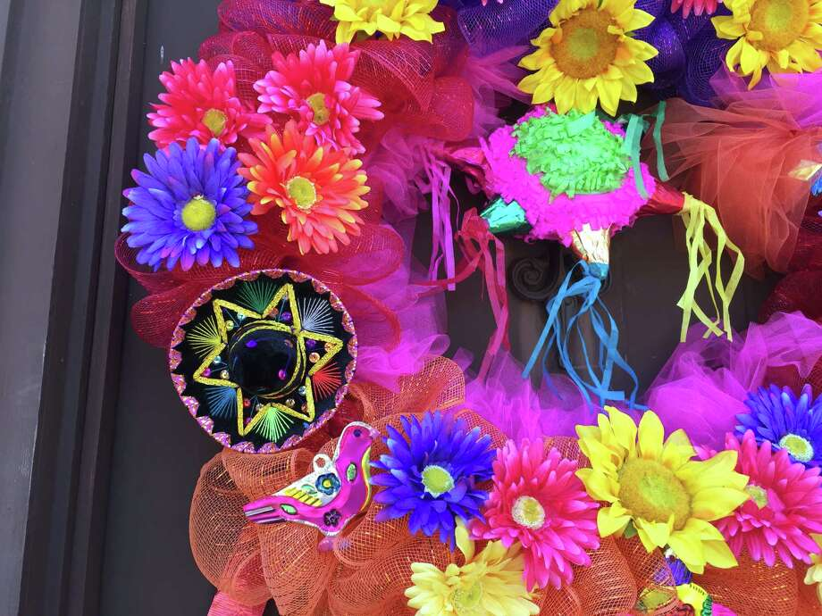 I hung two mini piñatas, one in the center of the wreath and one dangling from the bottom, for a fun pop. I also glued small velvet sombreros and punched tin ornaments. Photo: Emily Spicer /San Antonio Express-News