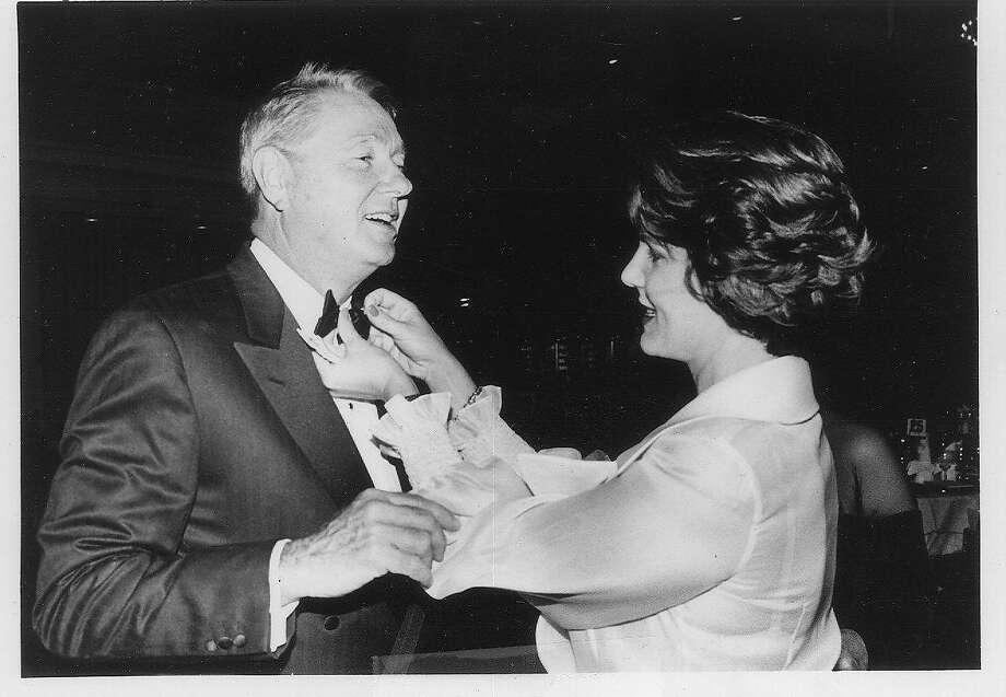 Katie JARMAN helps husband CLAUDE JARMAN with his tie