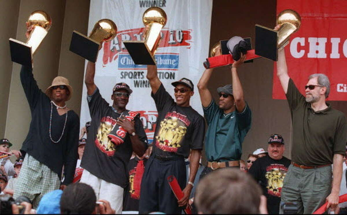 The Chicago Bulls' Dennis Rodman, left, Michael Jordan, Scottie Pippen, Ron Harper and coach Phil Jackson, right, hoist the team's five NBA Championship trophies aloft during a celebration in Chicago's Grant Park on June 16, 1997. The Chicago Bulls, a dynasty unlike anything seen in any pro sport since the '60s, go for a sixth title in their final season under coach Phil Jackson, marking the end of an era.