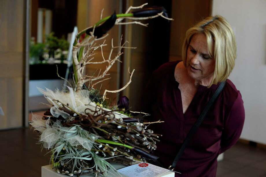 "Peggy Holmes looks at a plant sculpture on display at the Magnolia Garden Club's ""Birds & Blooms"" show at the Art Museum of Southeast Texas on Wednesday. The sculpture was created entirely from plant materials. Photo taken Wednesday 4/6/16 Ryan Pelham/The Enterprise Photo: Ryan Pelham / ©2016 The Beaumont Enterprise/Ryan Pelham"