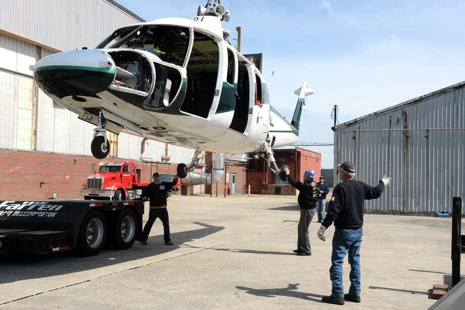 A Sikorsky S76 helicopter is lifted off of a flatbed trailer at the Connecticut Air and Space Center, in Stratford, Conn. April 6, 2016. The helicopter will be used for parts in the restoration of some of the center's other aircraft. Photo: Ned Gerard / Hearst Connecticut Media / Connecticut Post