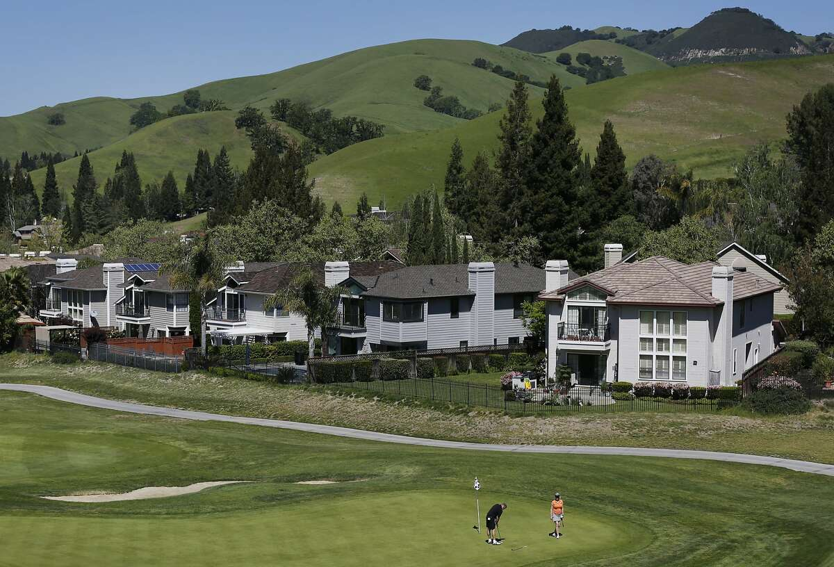 Homes can be seen in the background as people golf in Blackhawk April 6, 2016 in Danville, Calif.