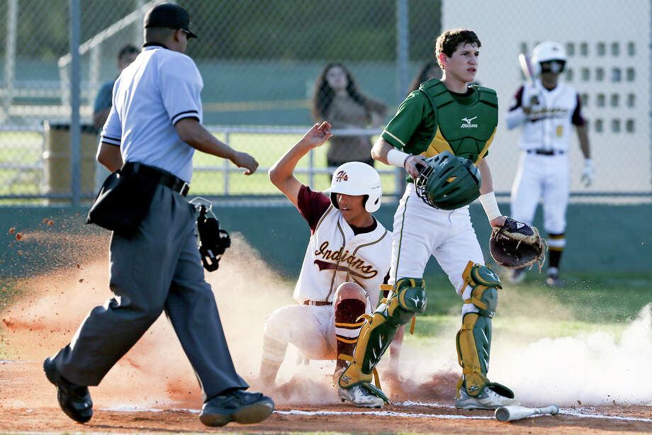 Harlandale's Nathan Reyes slides into home plate as McCollum catcher Jason Zertuche looks toward the field during the first inning of their 28-5A game at the Tejada Sports Complex on Thursday, March 31 2016.  Harlandale beat McCollum 8-2.  MARVIN PFEIFFER/ mpfeiffer@express-news.net Photo: Marvin Pfeiffer, Staff / San Antonio Express-News / Express-News 2016