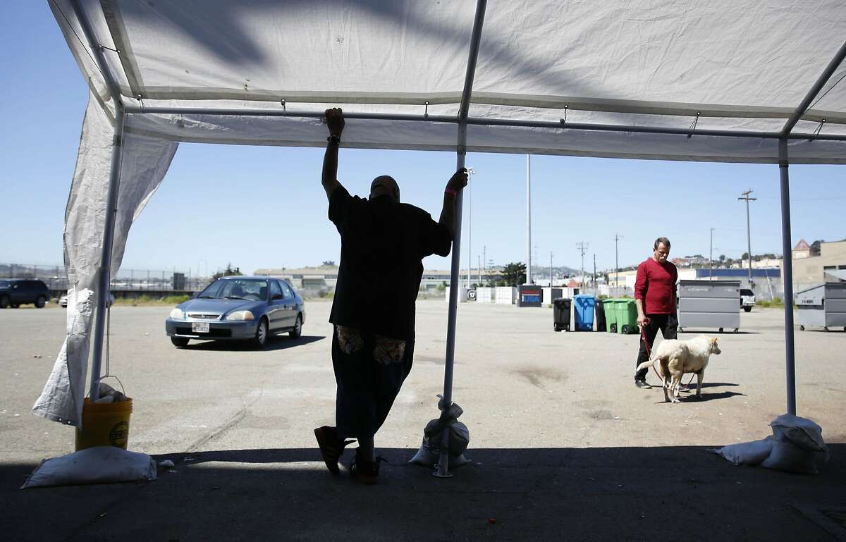 Henry Harris (l to r) stands under a canopy as Dave Tompkins walks his dog Betty at the Pier 80 homeless shelter on Wednesday, April 6, 2016 in San Francisco, California. Mayor Lee said that Pier 80 would be kept open until at least July 1.