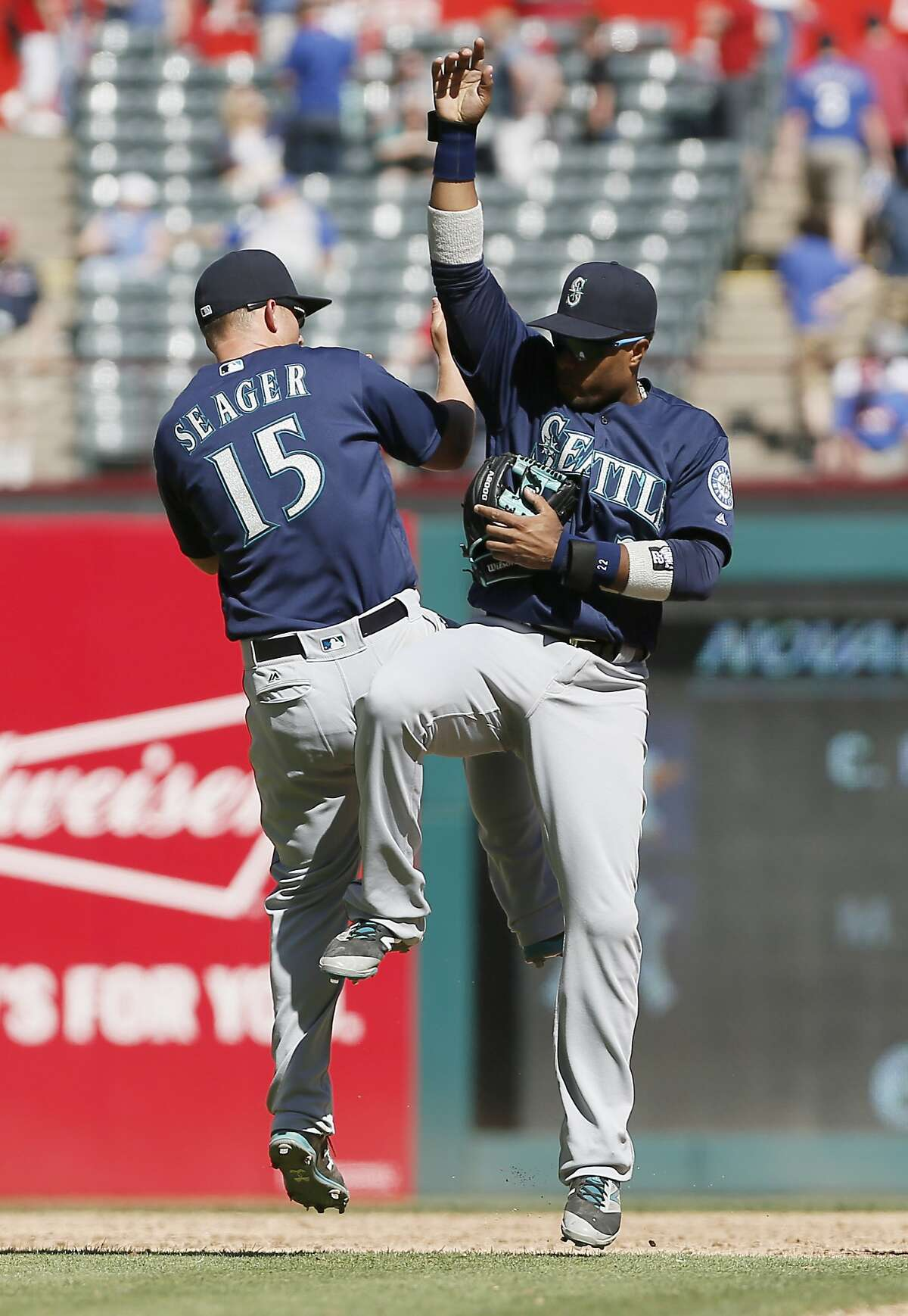 Seattle Mariners Kyle Seager (15) and Robinson Cano, right, celebrate a 9-5 win over the Texas Rangers after a baseball game, Wednesday, April 6, 2016, in Arlington, Texas. (AP Photo/Brandon Wade)